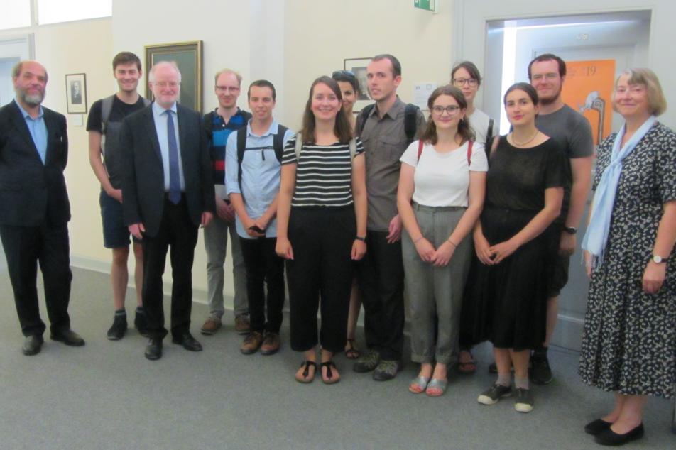 Arno Mentzel-Reuters, Leiter von Bibliothek und Archiv der MGH(links) und Martina Hartmann, Präsidentin der MGH (rechts)stellen den Gästen aus Frankreich die MGH vor.